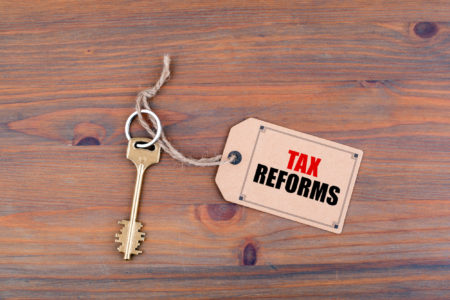 Key and a note on a wooden table with text - Tax Reforms